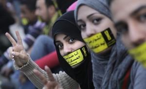 """Arabische Mädchen mit Sticker auf dem Gesichtschleier mit dem Slogan """"Nein - keine Militärversuche an Zivilisten"""" während der Proteste in Kairo auf dem Tahrir-Platz. Foto: AP Photo/Amr Nabil"""